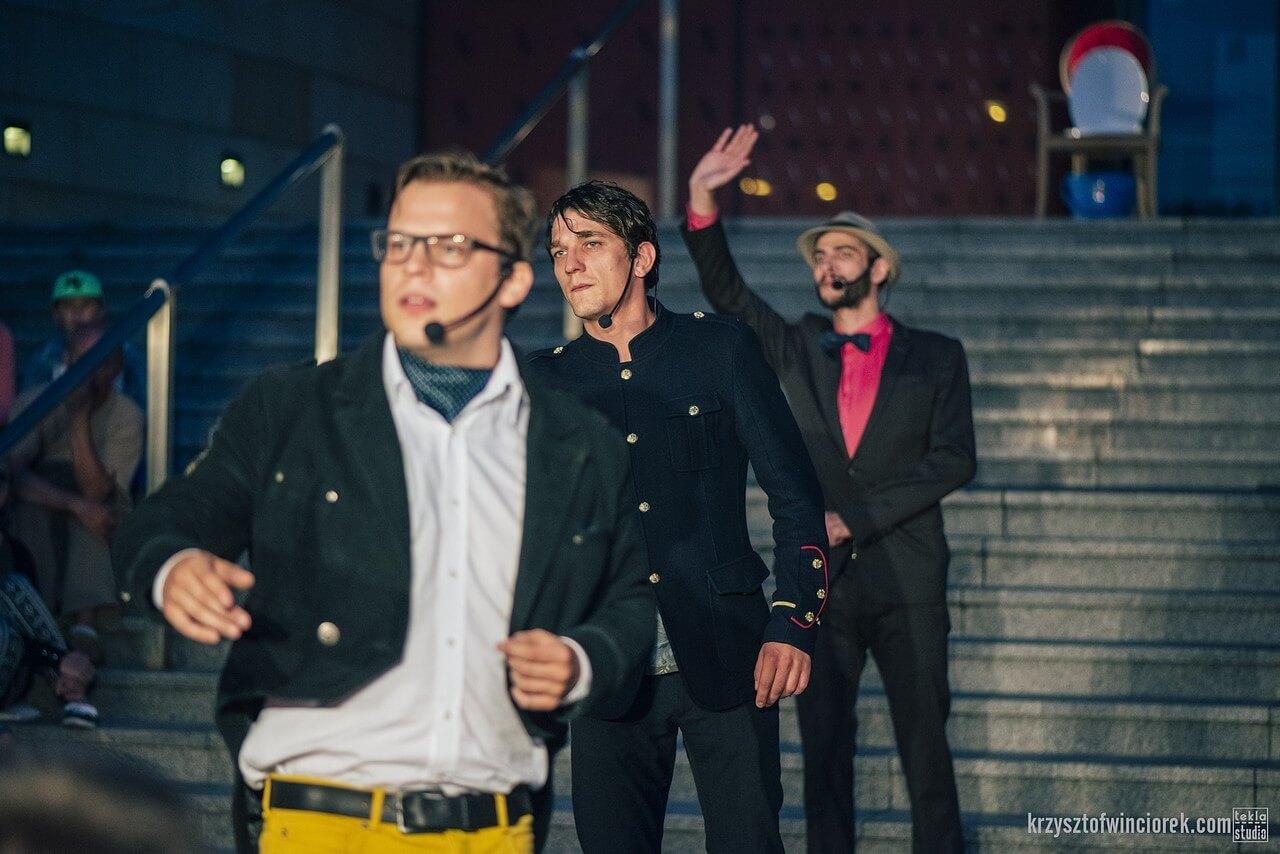 Zdjęcie do spektaklu Epitafium dla władzy. Trzech aktorów ustawionych jeden za drugim, ostatni podnosi rękę w geście powitania.