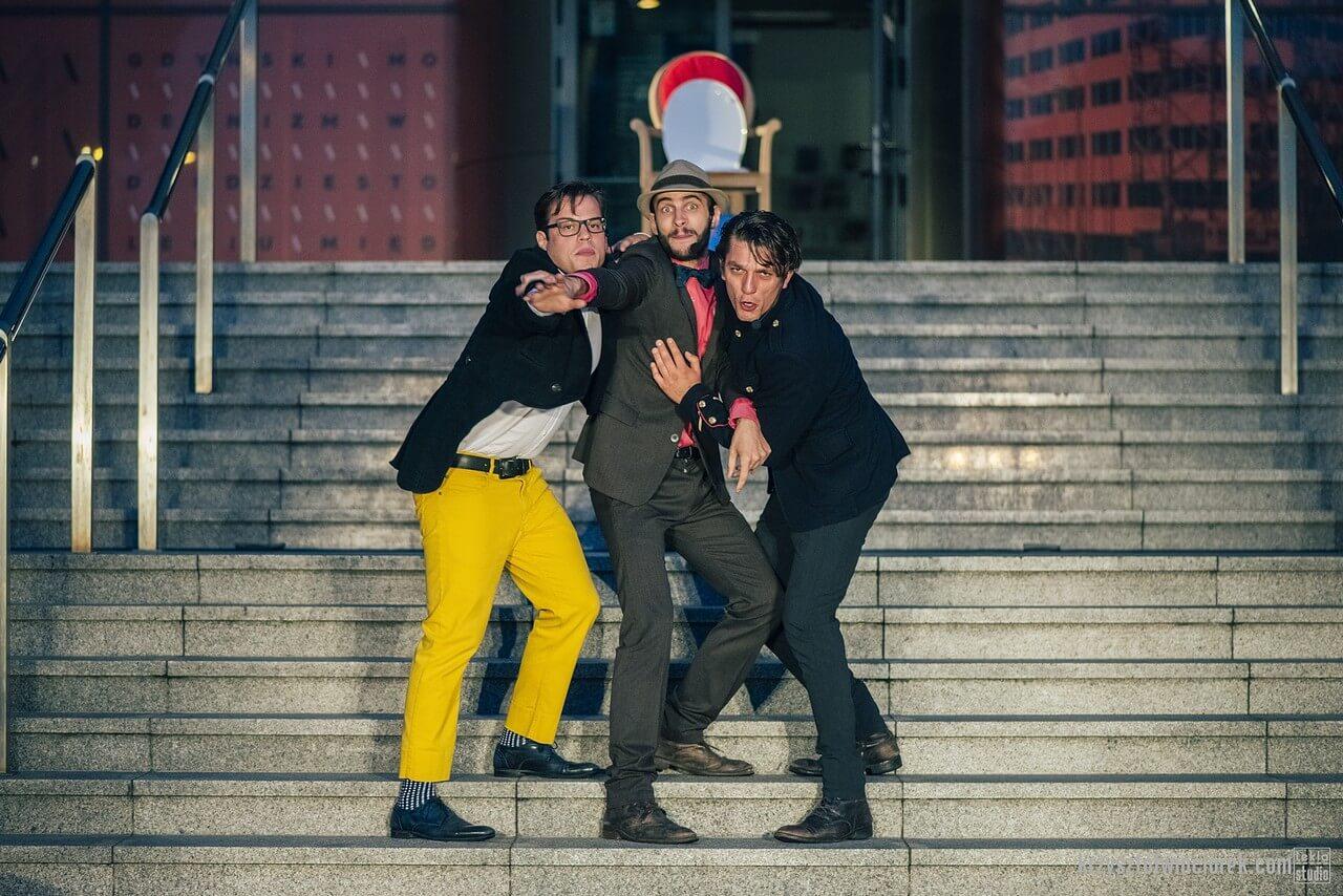 Zdjęcie do spektaklu Epitafium dla władzy. Trzech aktorów stoi na schodach. Ci po bokjach odciagają srodkowego do tyłu.