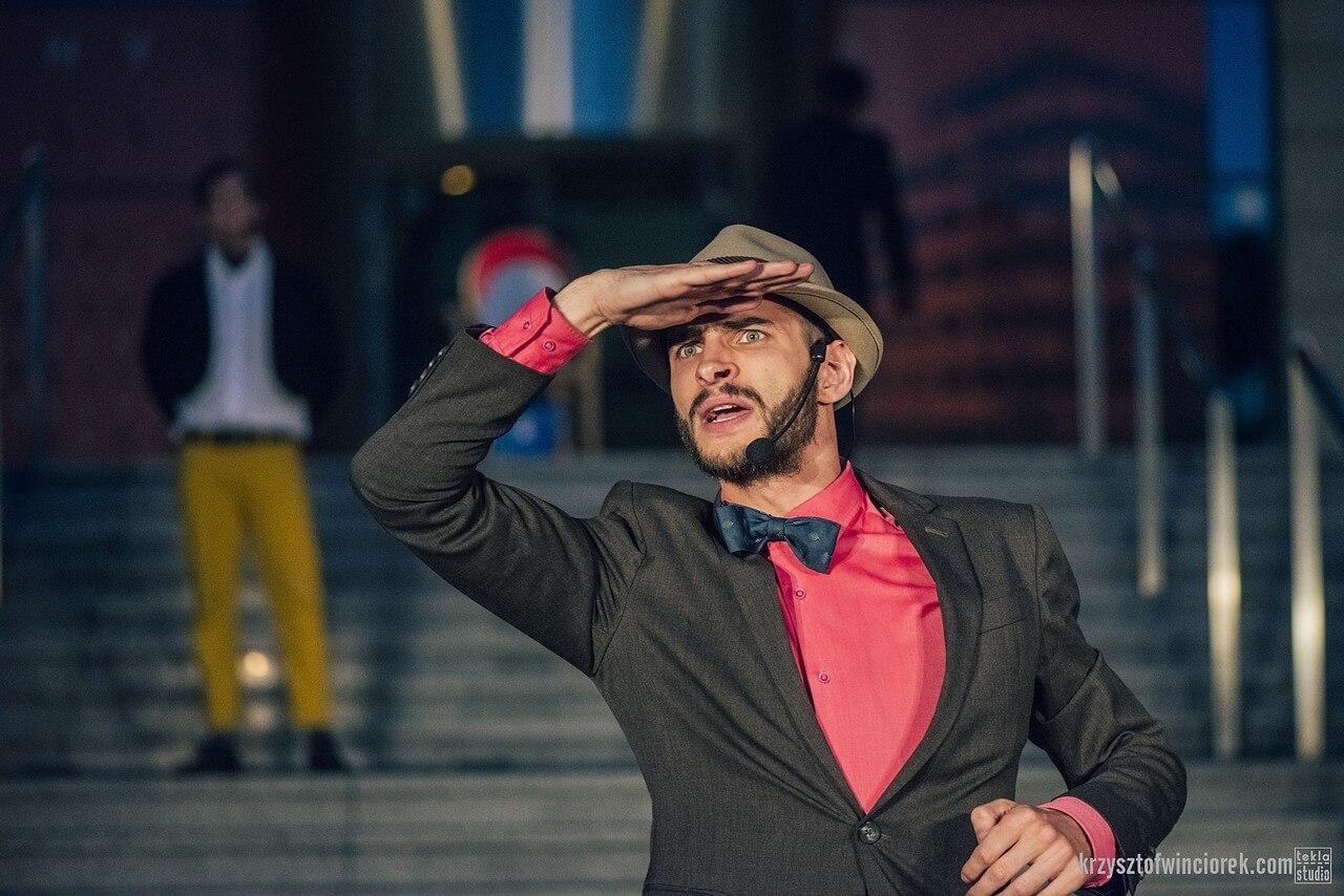 Zdjęcie do spektaklu Epitafium dla władzy. Aktor w kapeluszu, ciemnym garniturze, ró.zowej koszuli i niebieskiej muszce prawa reka osłania oczy od słońca.