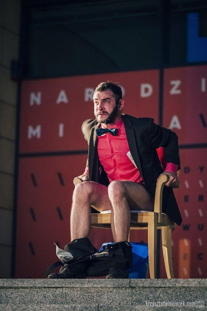 Zdjęcie do spektaklu Epitafium dla władzy. Aktor w rózowej koszulio siedzi na tronie imitujacym toaletę. Twarz wskazuje na duże napiecie.