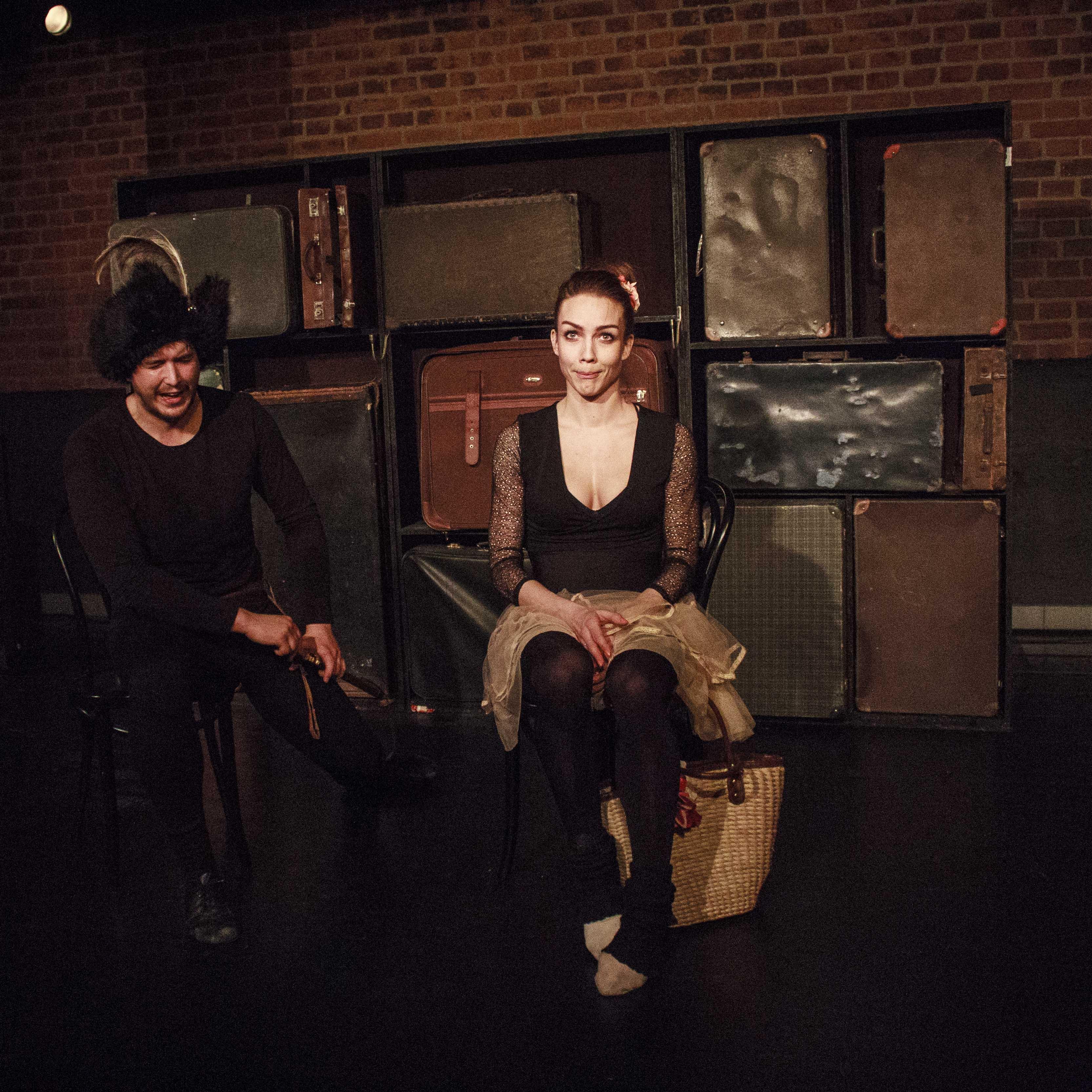 Zdjecie do spektaklu Emigrantka. Mężcyzna po lewo w futrzanej czapcez piórem i szablą przy boku. Po prawo aktorka z wyplataną torbą.