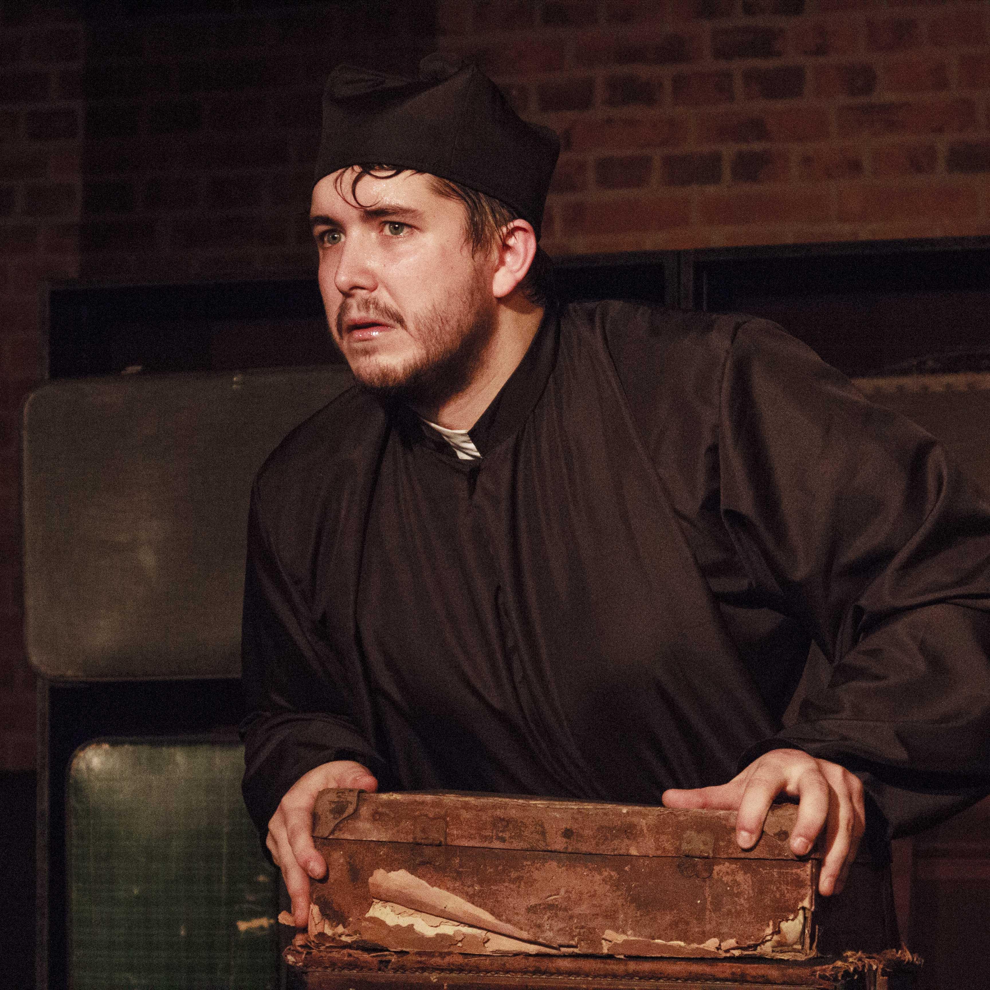 Zdjecie do spektaklu Emigrantka. Aktor przebrany za księdza. Ręce opiera o drewnianą skrzynkę.