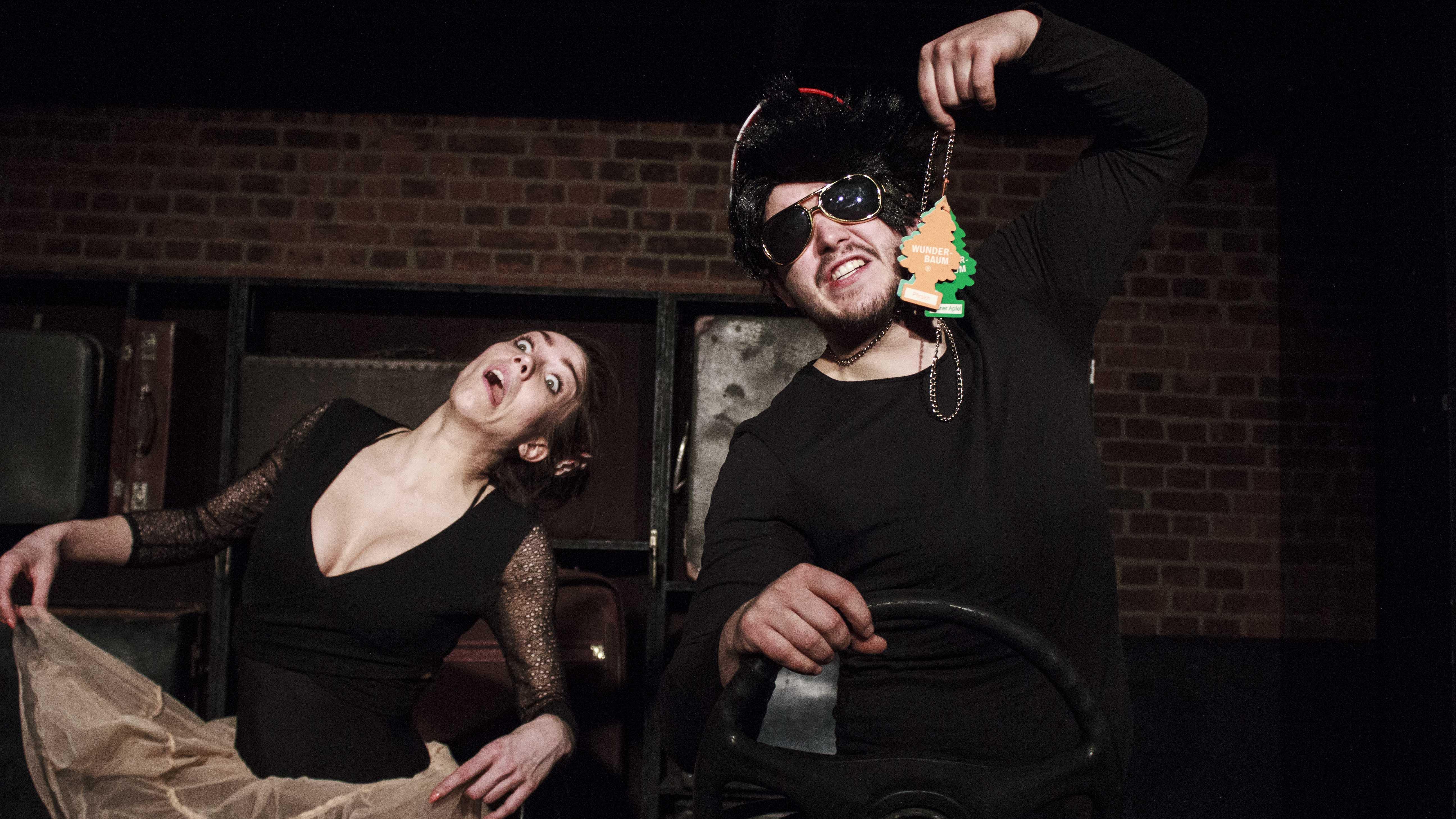 Zdjecie do spektaklu Emigrantka. Aktor po prawo trzyma w ręku samochodowe odświeżacze, kobieta po lewo trzyma się za sukienkie, wytrzeszcza oczy i pokazuje język.