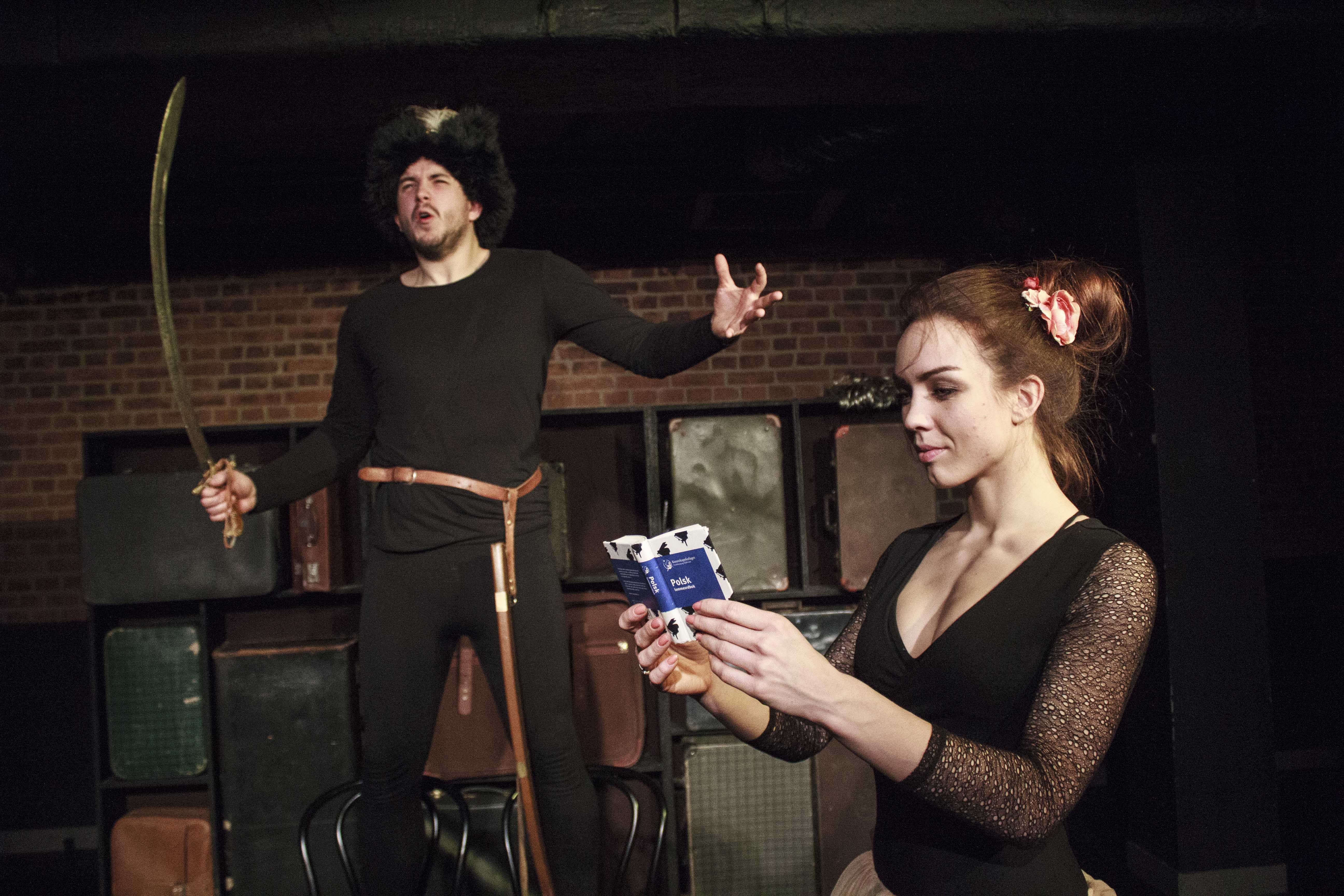 Zdjecie do spektaklu Emigrantka. Mężczyzna w futrzanej czapce z piórem i szabla w reku stoi po lewej stronie. Z prawej na pierwszym planie aktorka czytajaca mały słownik.