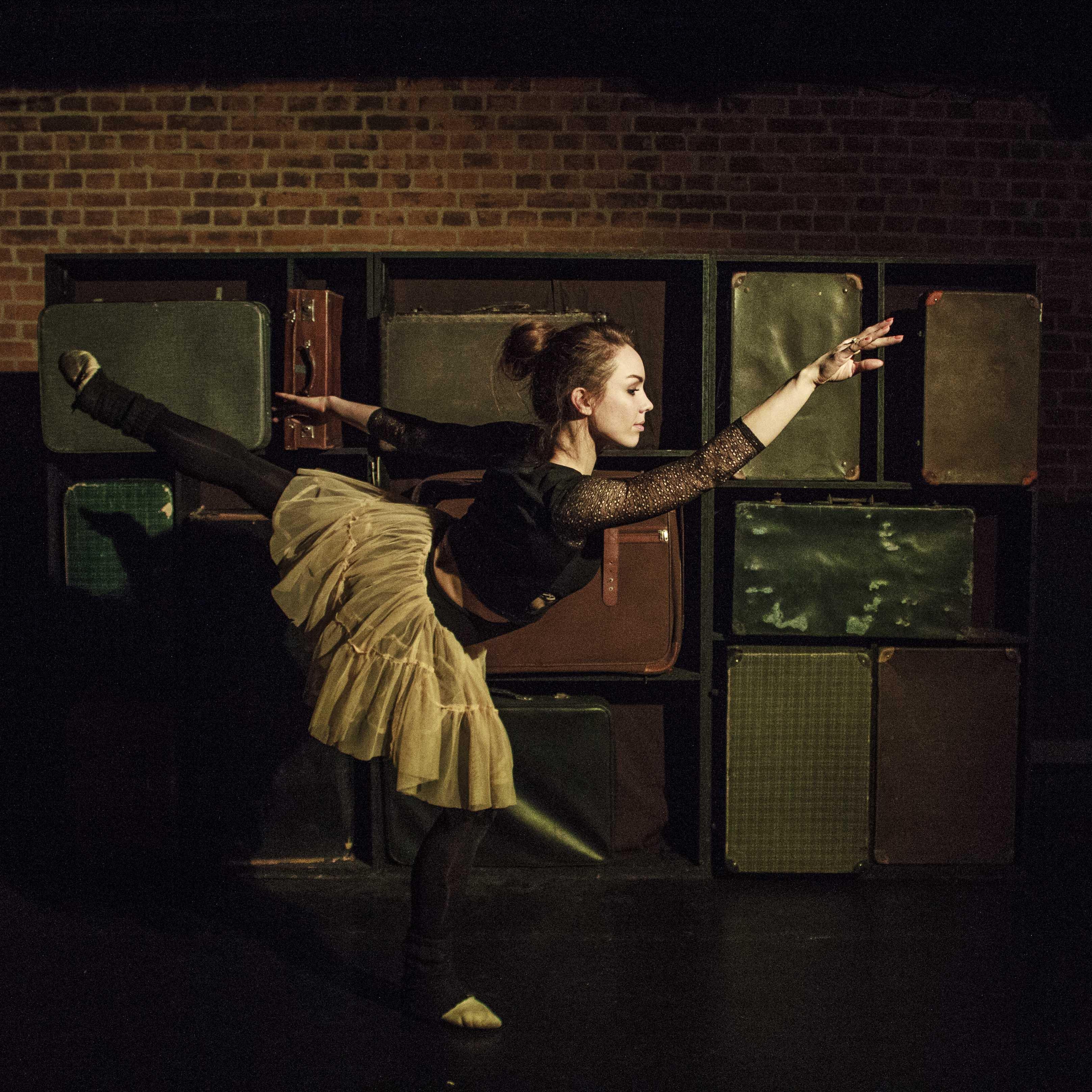 Zdjecie do spektaklu Emigrantka. Aktorka w stroju baletnicy w pozie. Stoi na jednej nodze. Druga noga wyciagnieta do tyłu, reka do przodu.