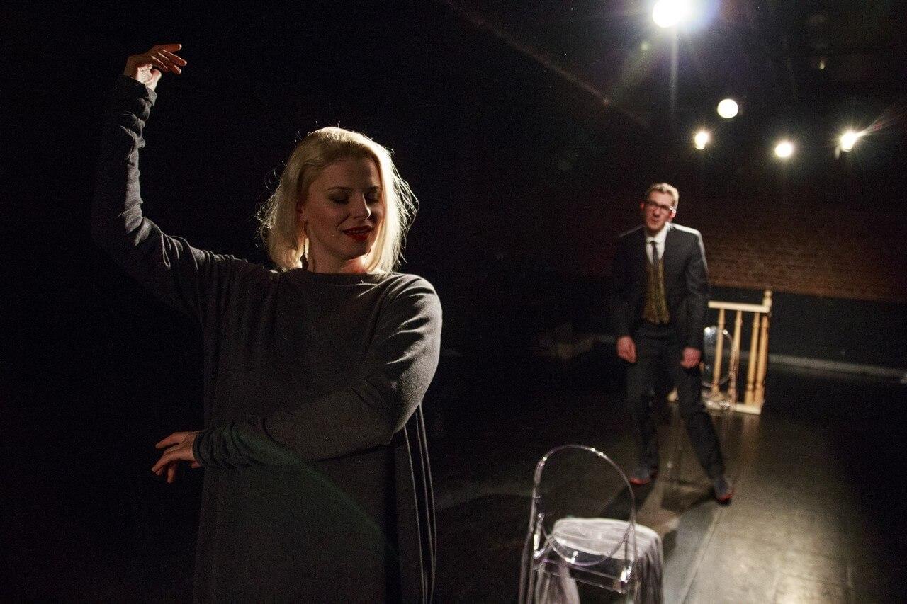 Zdjecie do spektaklu Batszeba. Na pierwszym planie kobieta w czerni tanczy. Z tyłu mężczyzna w garniturze się jej przygląda.