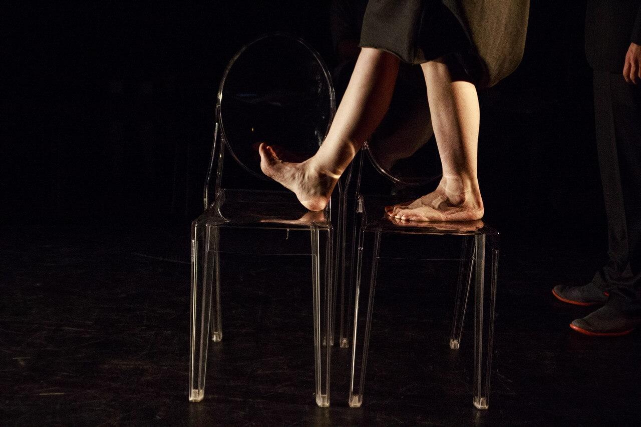 Zdjecie do spektaklu Batszeba. Widać stopy kobiety idącej po przezroczystych kszesełkach.