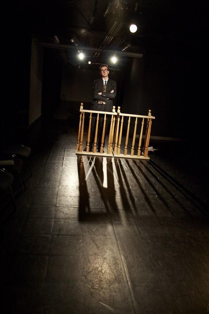 Zdjecie do spektaklu Batszeba. Meżczyzna w czarnym garniturze stoi za drewnianymi jasnymi barierkami.