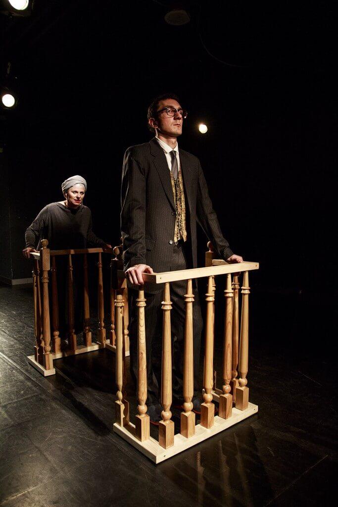 Zdjecie do spektaklu Batszeba. Mężczyzna w czarnym garniturze wsparty o drewniana barierkę, za nim kobitea w czaerni i w turbanie, również wsparta o barierke.