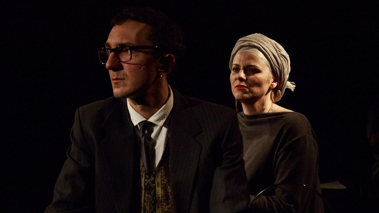 Zdjecie do spektaklu Batszeba. Mężczyzna w okularach i garniturze. Kobieta ma na głowie turban.