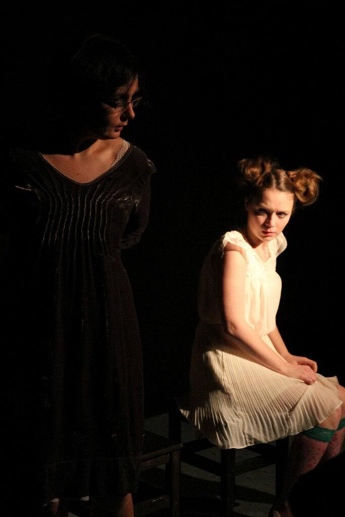 Zdjecie do spektaklu Kawa, chleb i ser. Starsza aktorka ubrana na czarno stoi. Obok młodsza w białej sukience siedzi.