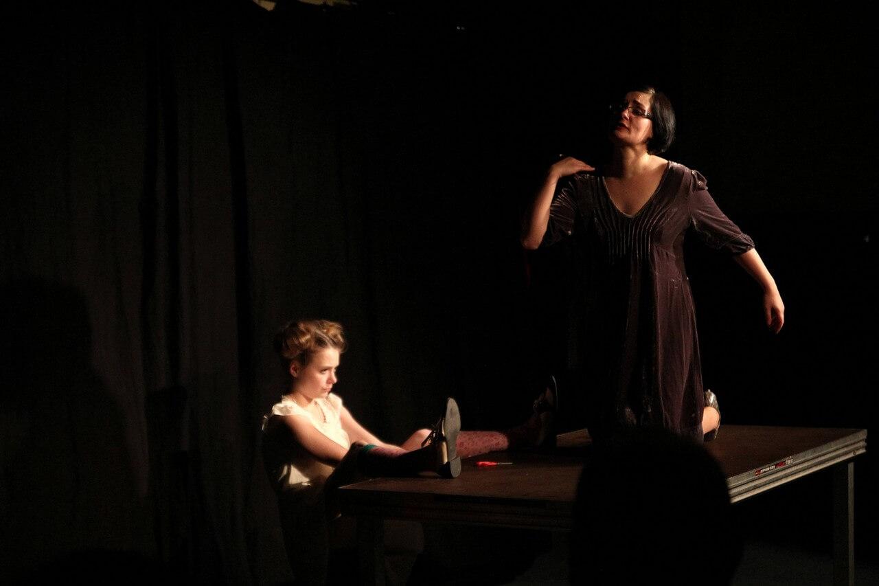 Zdjecie do spektaklu Kawa, chleb i ser. Aktorka w czarnej sukience klęczy na stole. Aktorka w białej sukience siedzi z lewej strony stolu z nogami zarzuconymi na blat.
