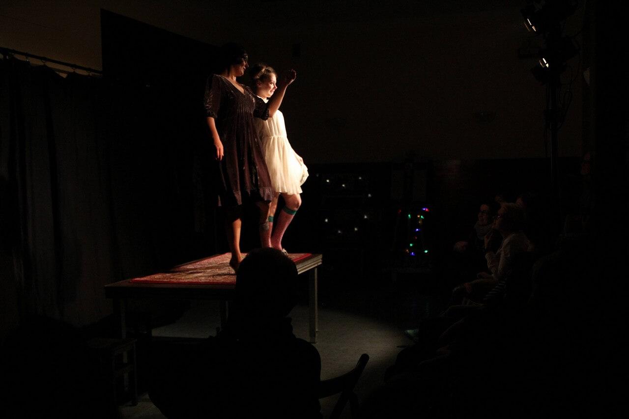 Zdjecie do spektaklu Kawa, chleb i ser. Aktorka w czarnej sukience i aktorka w białej sukience stoją na stole.