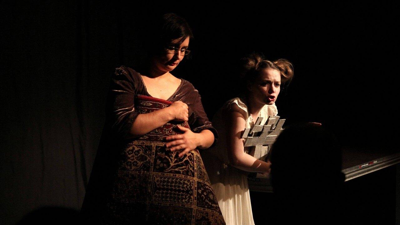 Zdjecie do spektaklu Kawa, chleb i ser. Aktorka z lewej trzyma i przycieska do siebie dywan. Aktorka w białej sukience stoi obok, pochylona do przodu, trzyma w objęciach szare krzyże.
