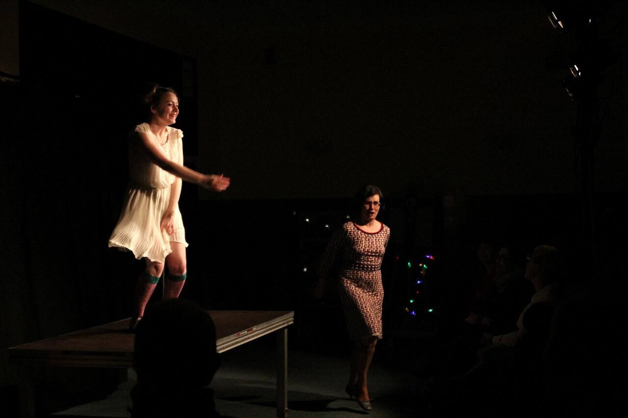 Zdjecie do spektaklu Kawa, chleb i ser. Aktorka w białj sukience tańczy na stole. Po prawo, na podłodze aktorka w kraciastej sukience - również tańczy.