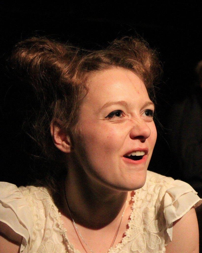 Zdjecie do spektaklu Kawa, chleb i ser. Młoda aktorka z grymasem na twarzy. W białej sukience na ramiączkach.