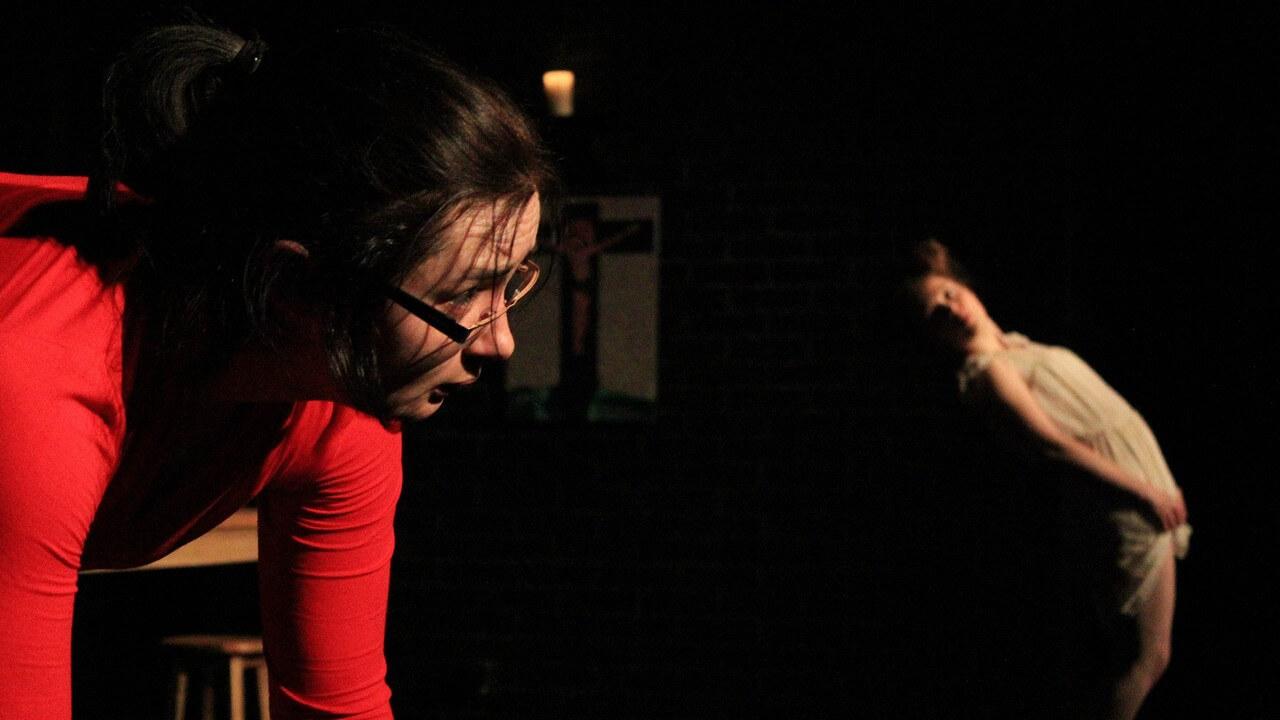 Zdjecie do spektaklu Kawa, chleb i ser. Na pierwszym planie aktorka, w czerwonej bluzce pochylona do przodu. Z tyłu aktorka w białej sukience odchyla się w tył.