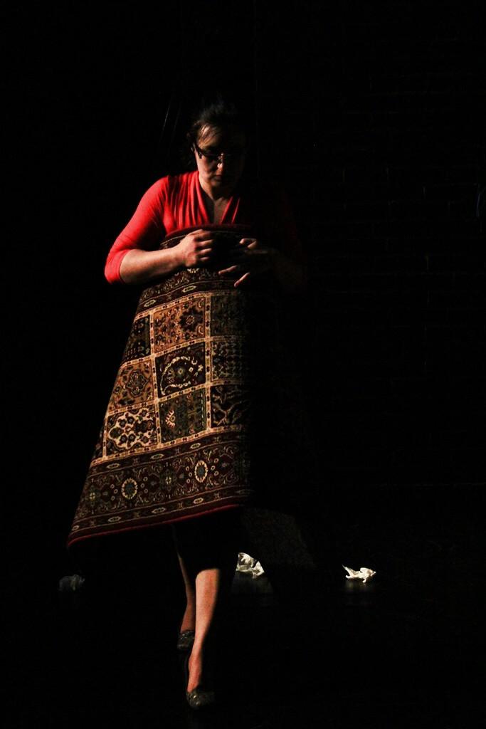 Zdjecie do spektaklu Kawa, chleb i ser. Aktorka owinięta w dywan jak w sukienkę.