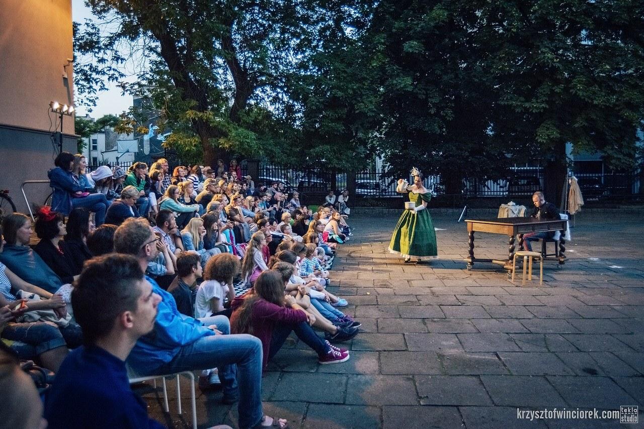 Z lewej strony publiczność siedzi na schodach przy poisku. Po prawej stronie aktorka w zielonej sukni królowej i aktor siedzący przy stole.