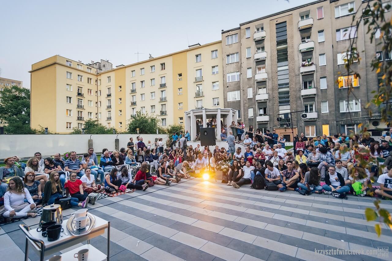 Publiczność zgromadzona na placu wśród blokowiska.