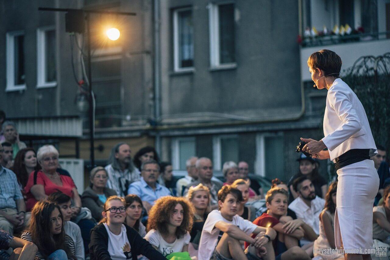 Aktorka w białym żakiecie i spudnicy przed widownią siedzącą na ziemi. W tle blok.