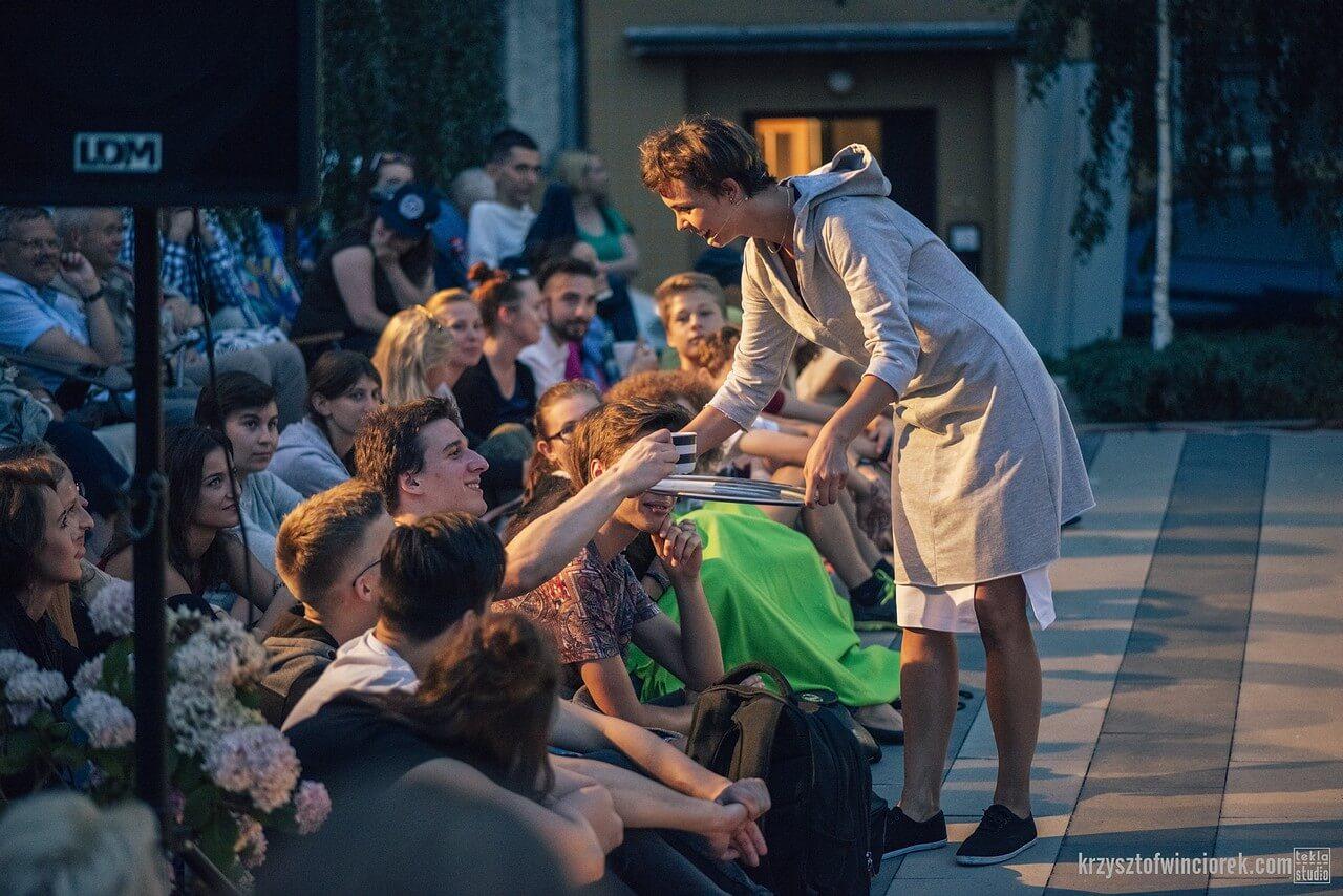 Aktorka podaje kawę, widzom siedzącym na ziemi.