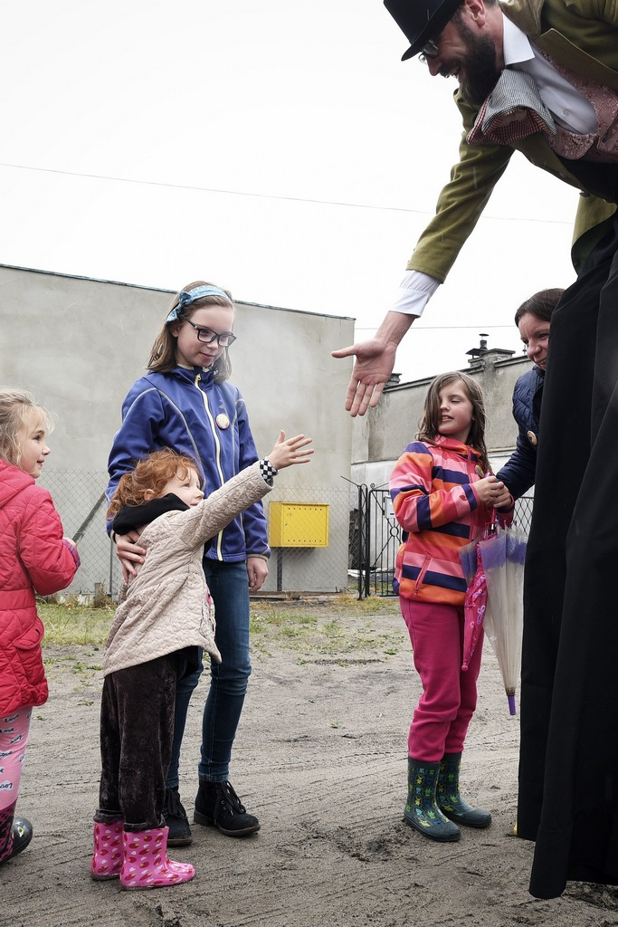 Aktor na szczudłach wyciaga rękę do dziewczynki jakby chciał się z nia przywitać.