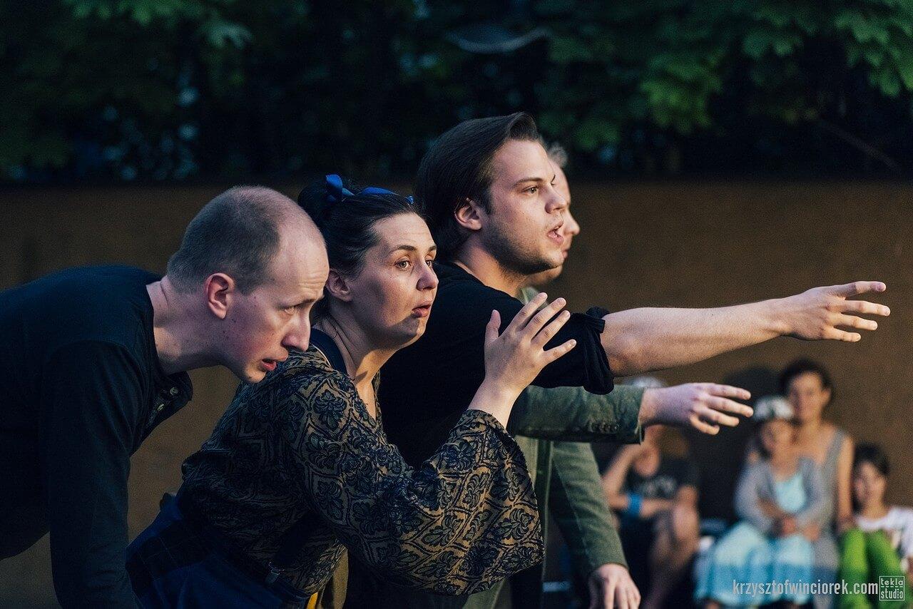 Czwórka aktorów stoi w rzędzie, wyciagają ręce przed siebie.