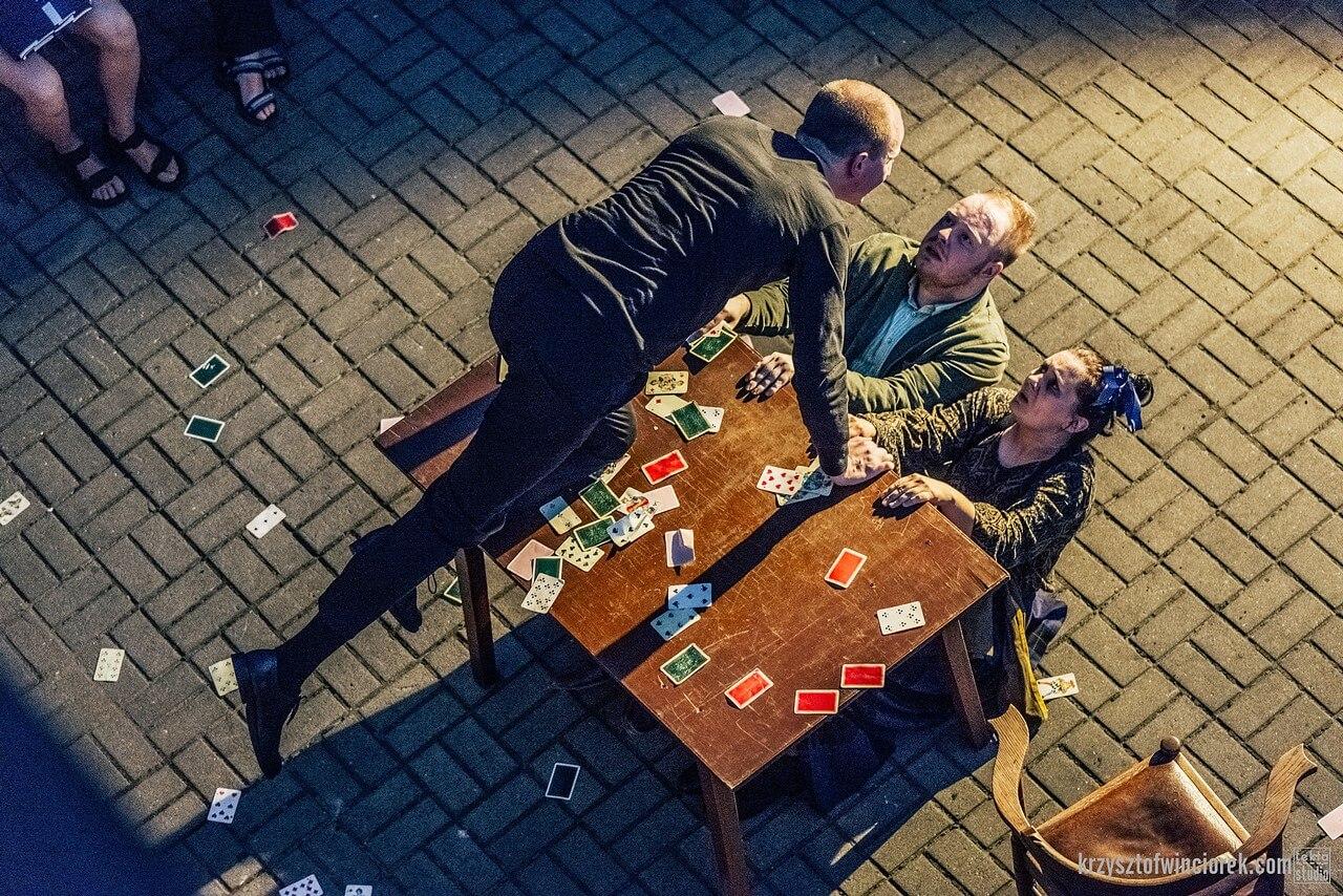 Aktor klęczy na stole i pochyla się w kierunku dwójki aktorów klęczących za stołem. Wszedzie leżą rozsypane karty do gry.