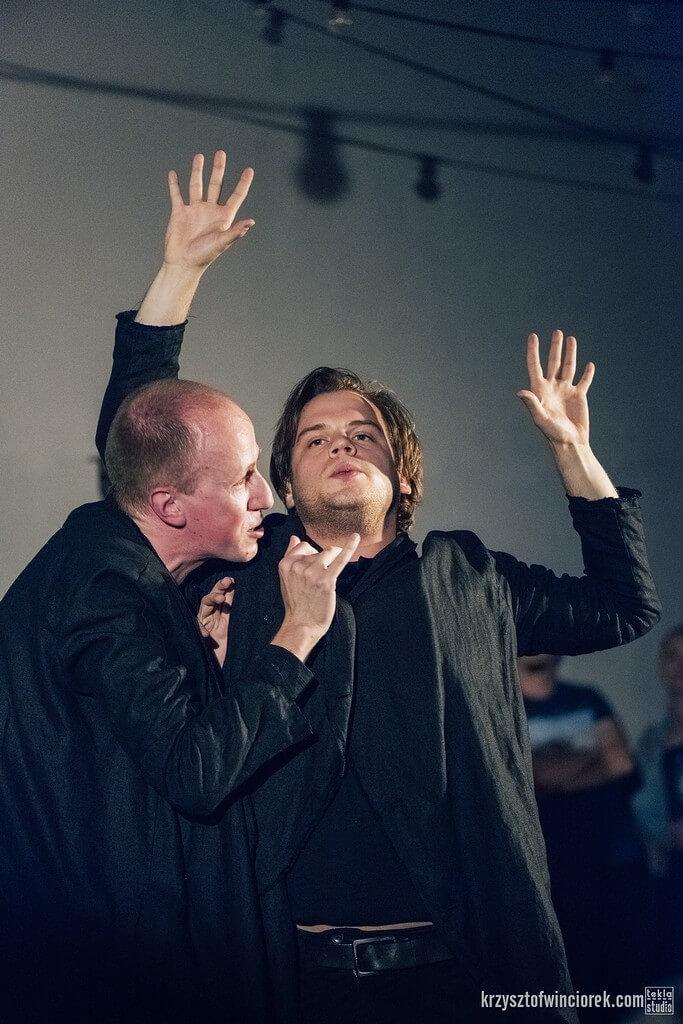 Na zdjęciu dwóch aktorów ubranych na czarno. jeden unosi ręce do góry. Drugi trzyma ręce przy jego kołnierzu.