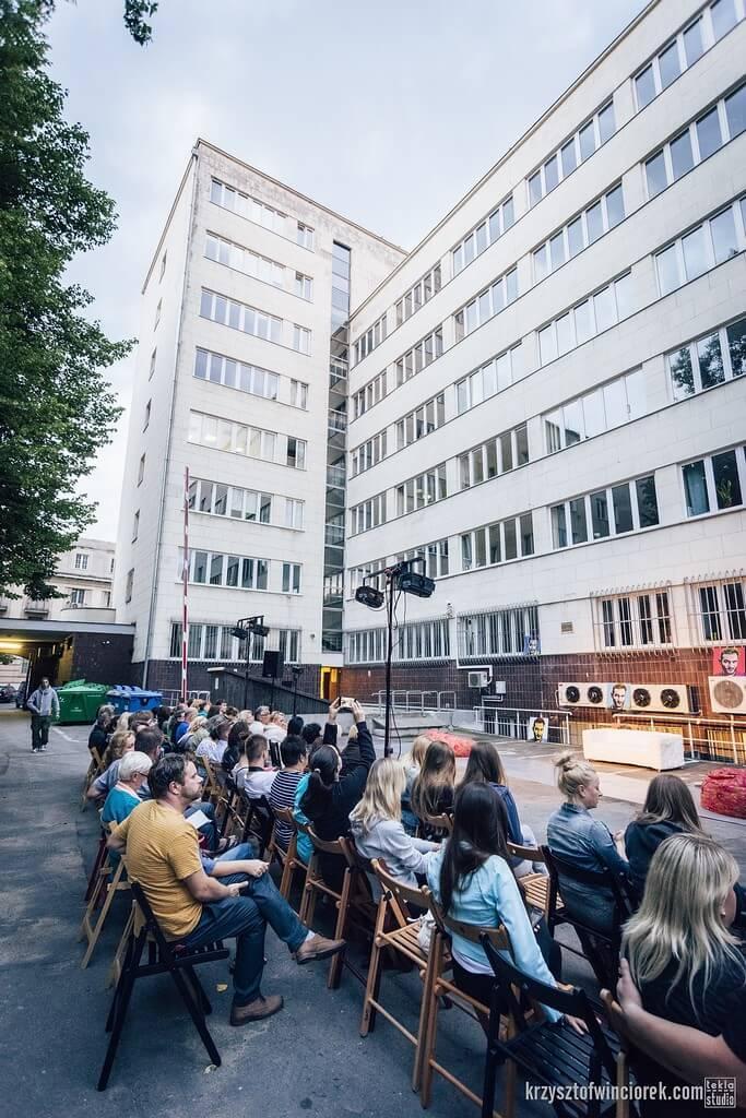 Publiczność siedząca na krzesełakch przy scenie zorganizowanej na placu przed wysokim budynkiem.