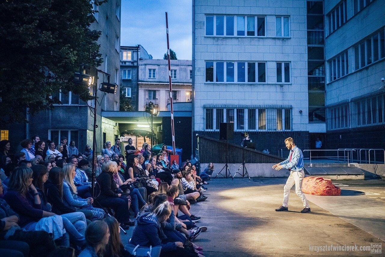 Spektakl w plenerze. Aktor w niebieskiej koszuli i białych spodniach przed publicznością zgromadzoną na placu. W tle kamienice.
