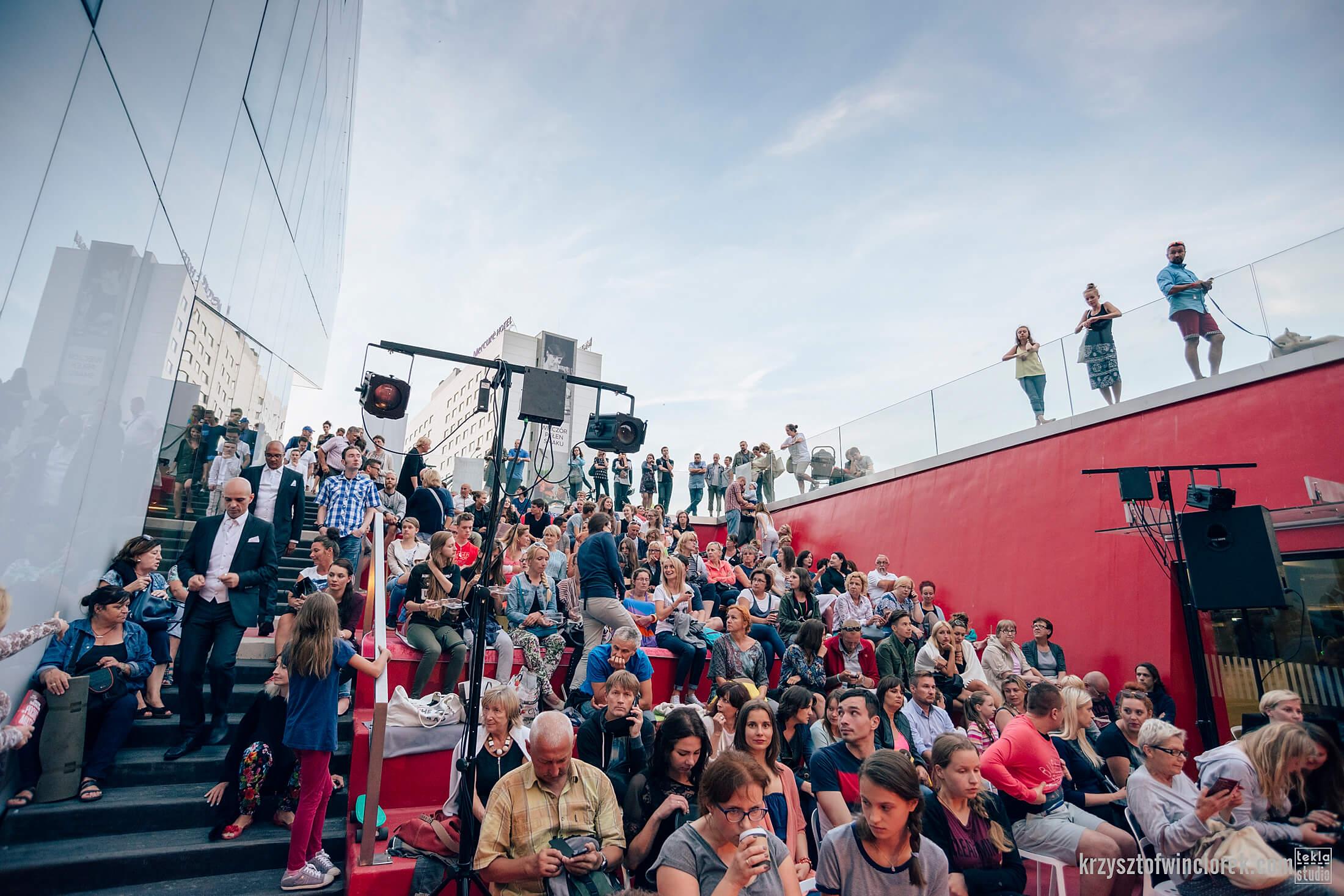 Publicznosc zgromadzona na schodach.