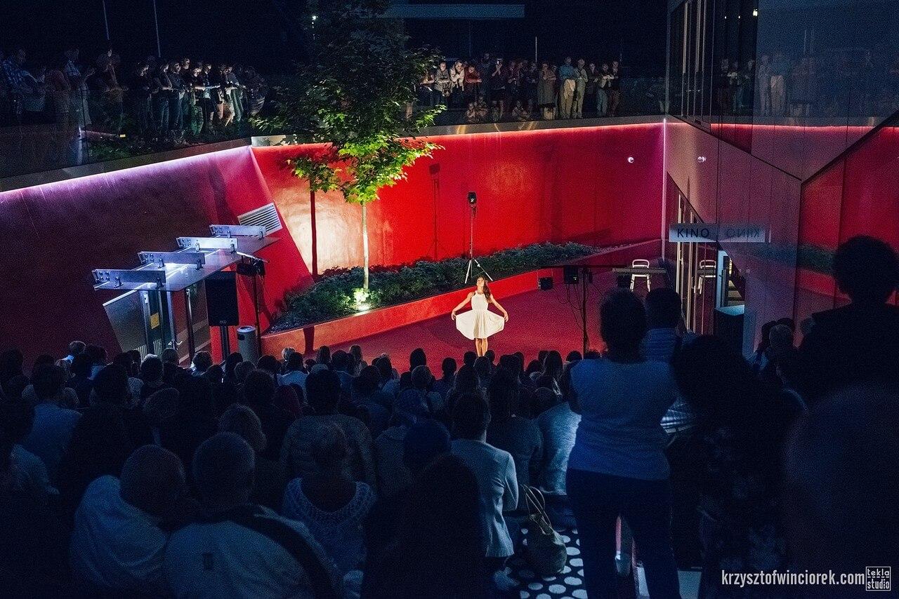 Aktorka, tancerka w białej skukience, stoi w czerwonej przestrzeni ook drezwa. Dookoła zgroadzona liczna publicznośc.