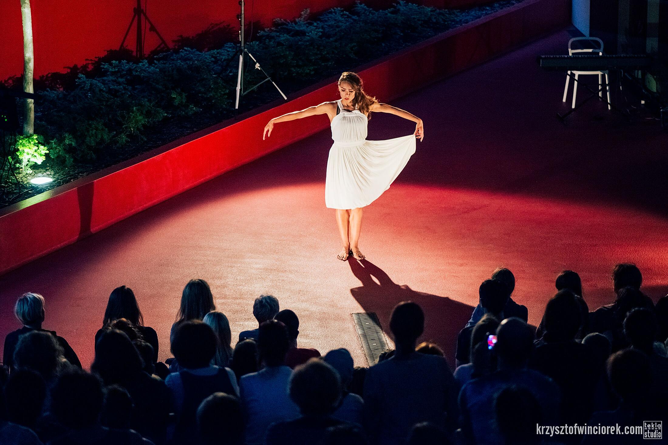 Aktorka tancerka w białej sukience. W lewej ręce trzyma rabek sukienki. Czeerwona podłoga, publicznośc zgromadzona przed aktorką.