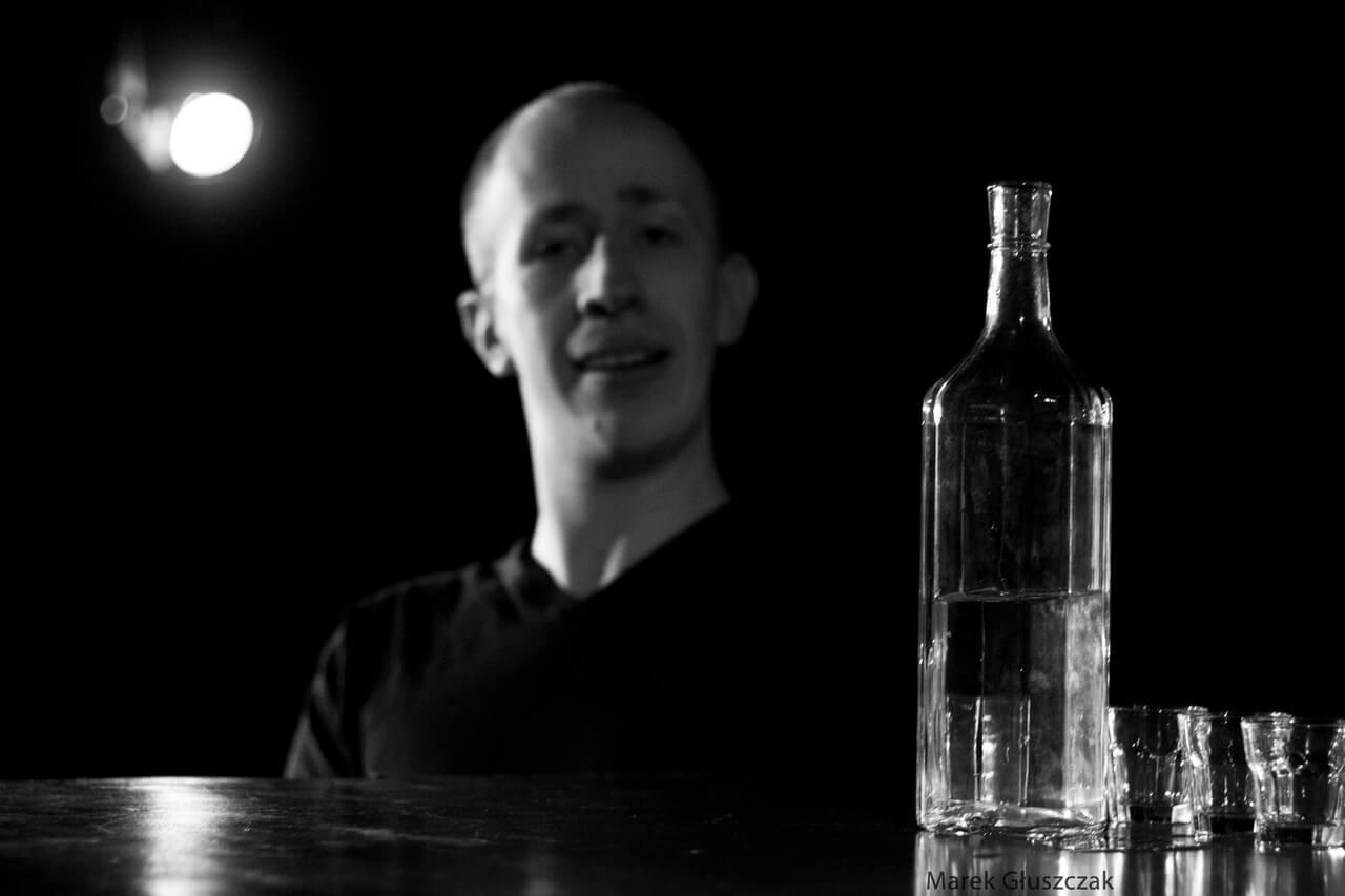 Zdjecie do spektaklu pomiędzy. Aktor patrzy na butelke i kieliszki stojące na pierwszym planie.