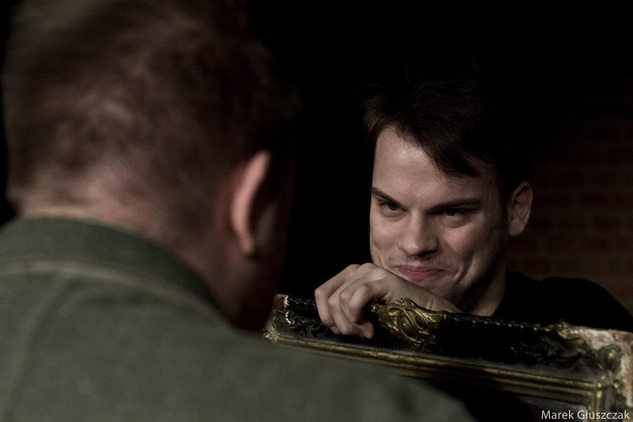 Zdjecie do spektaklu pomiędzy. Aktor usmiecha się do stojącego tyłem na pierwszym planie. Duże zblizenie.