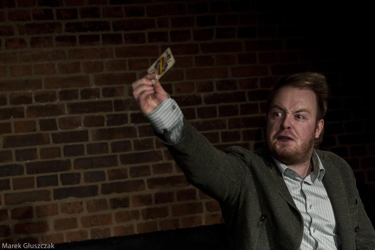 Zdjecie do spektaklu pomiędzy. Aktor z furia na twarzy unosi w reku kartę do gry.