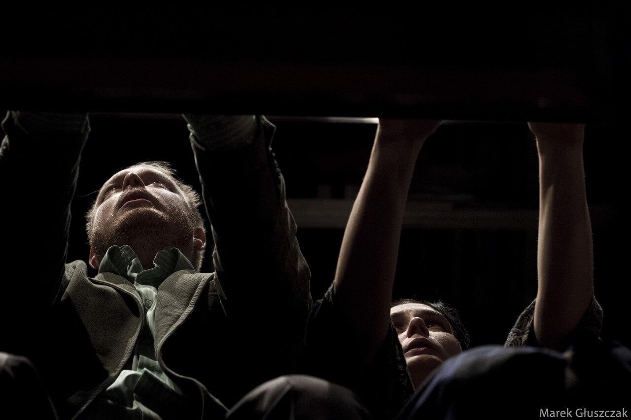 Zdjecie do spektaklu pomiędzy. Ujecie z dołu, z pod stołu. Widac aktora i aktorke z rekami trzymanymi na stole, patrzą na wprost.