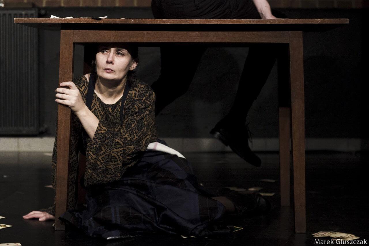 Zdjecie do spektaklu pomiędzy. Aktorka siedzi pod stołem. Trzyma się jego lewej nogi.