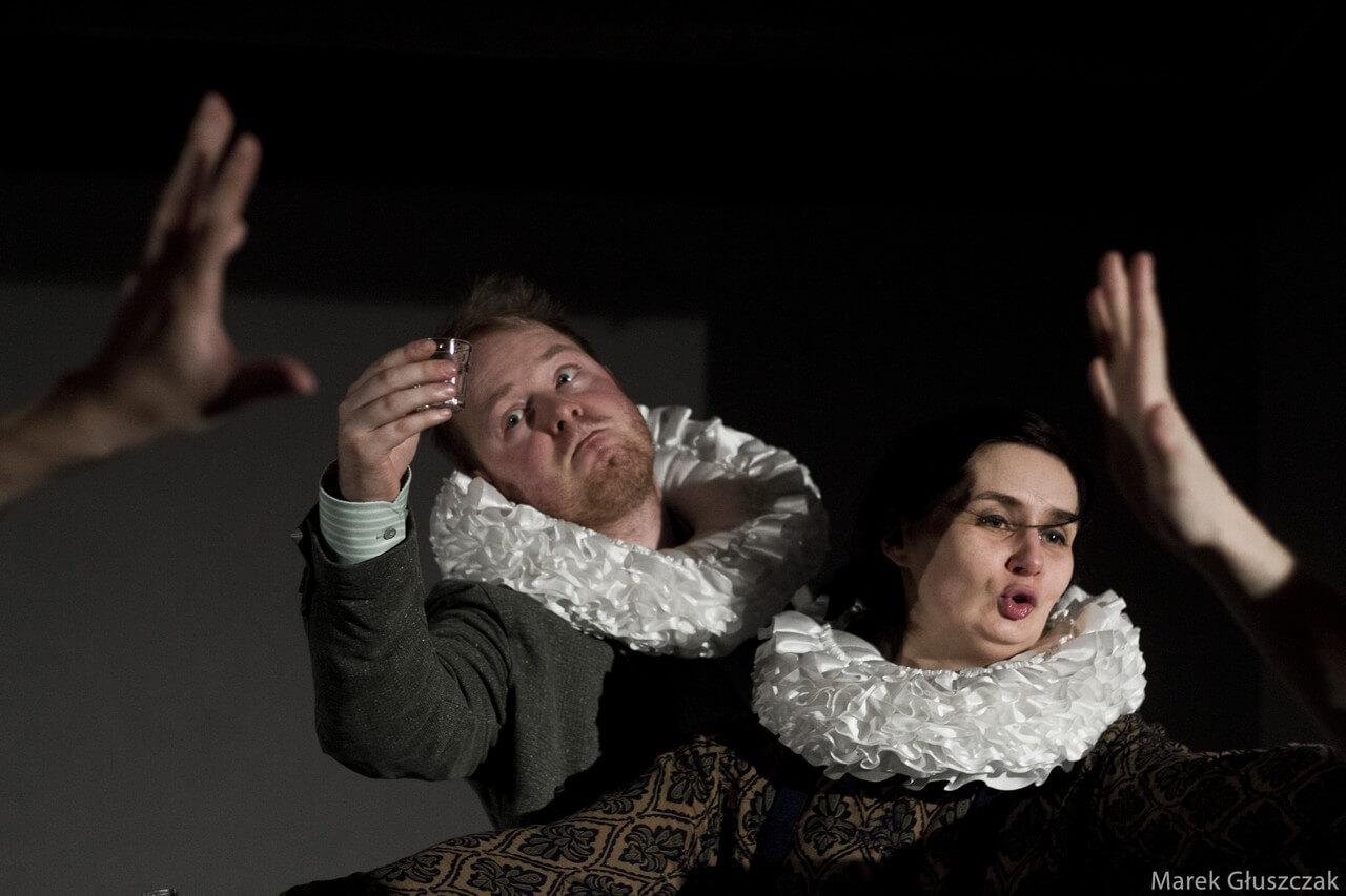 Zdjecie do spektaklu pomiędzy. Dwije aktorów z białymi kryzami na szyi. Tańczą, aktor trzyma kieliszek.
