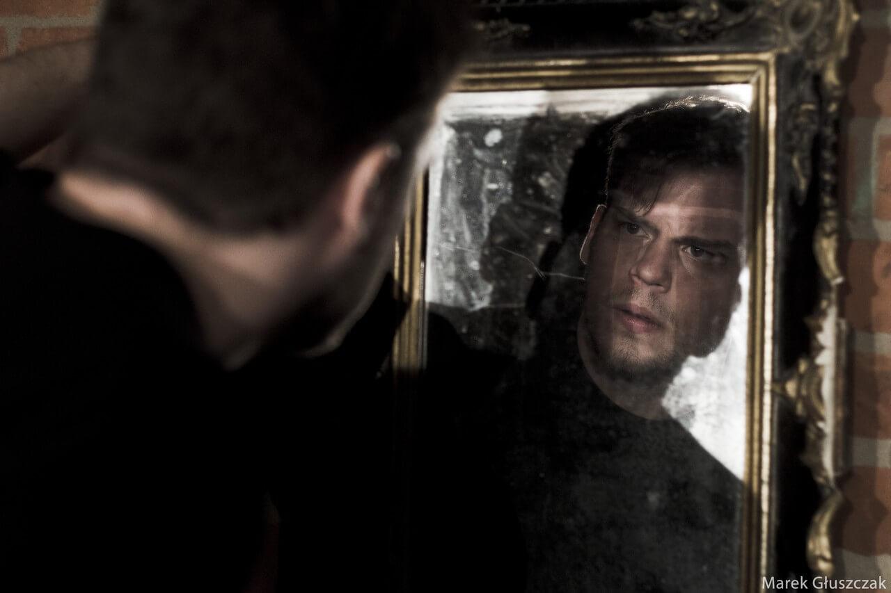 Zdjecie do spektaklu pomiędzy. Aktor przegląda się brudnym lustrze.