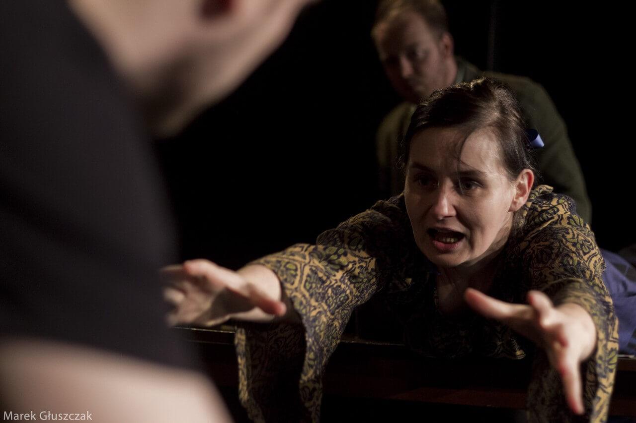 Zdjecie do spektaklu pomiędzy. Aktorka wyciaga ręce w kierunku aparatu. Ma otwarte usta.