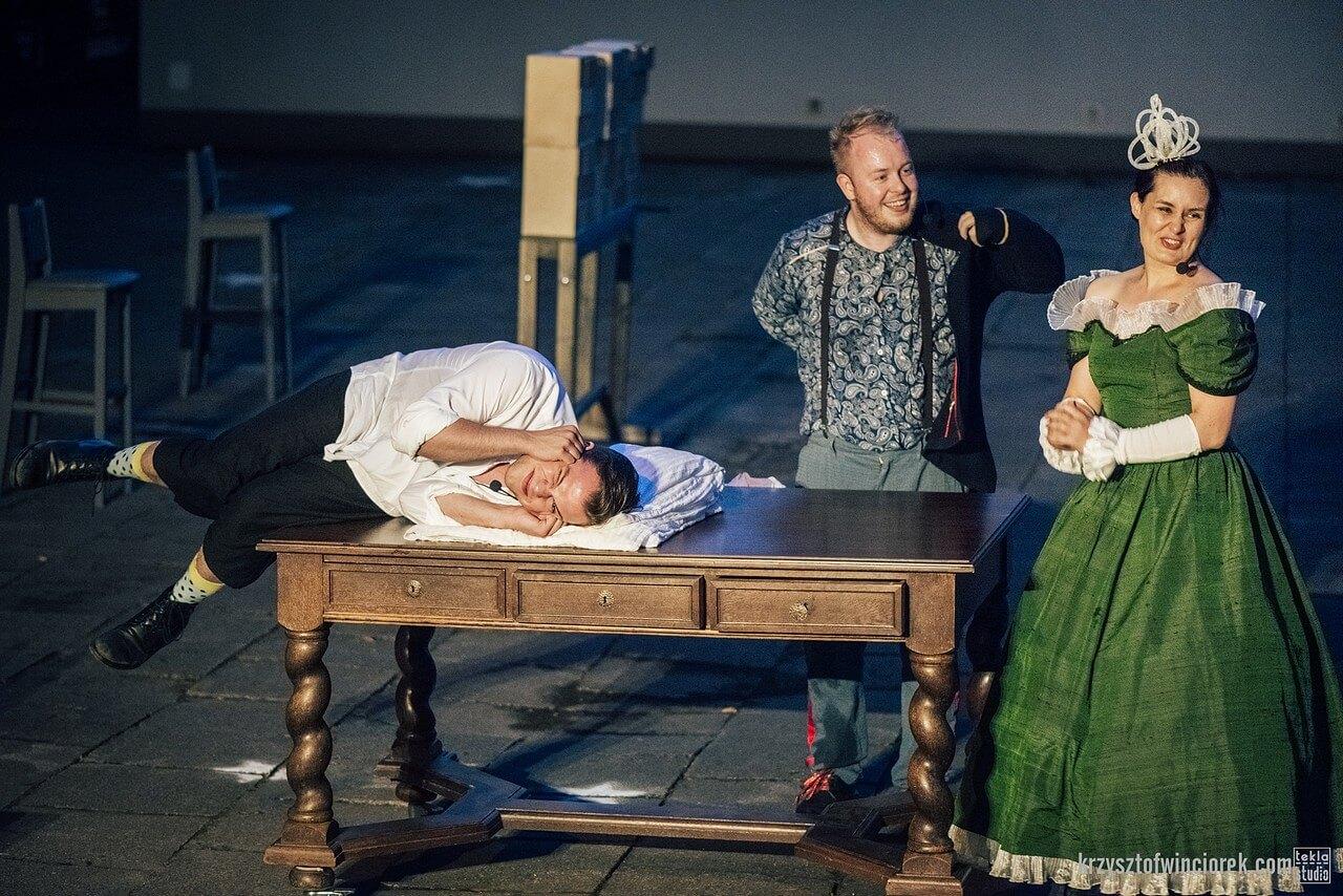 Aktor lezy na stole i zasłania rękami uszy. Obok aktorka przebrana za królową w zielonej sukni, drugi aktor zakłada marynarkę - usmiechają się