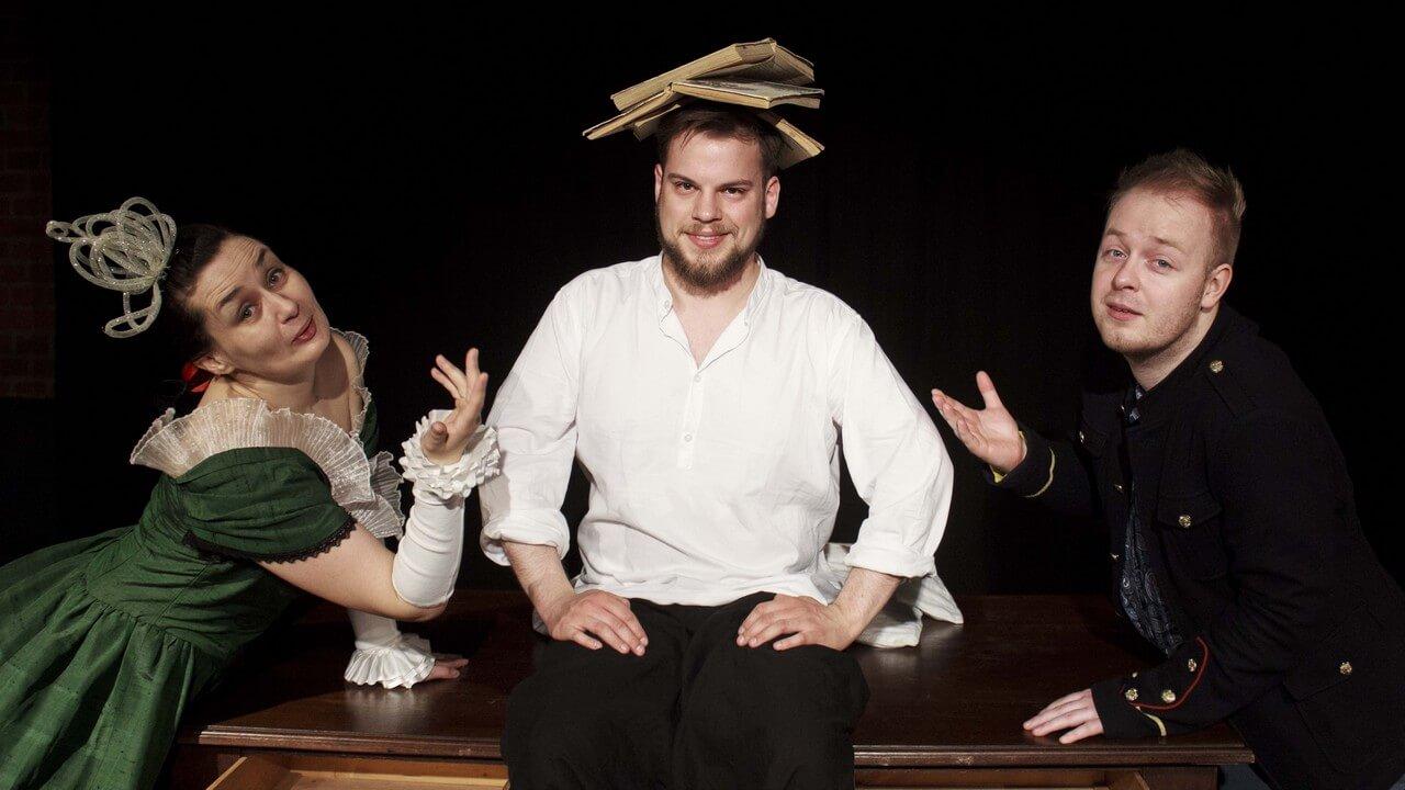 Na zdjęciu trójka aktorów. Z lewej aktorka przebrana za królową w zielonej sukni, po srodku aktor w białej koszuli z trzema ksiazkami na głowie, po prawo aktor w czarnej marynarce z uniesioną ręką.