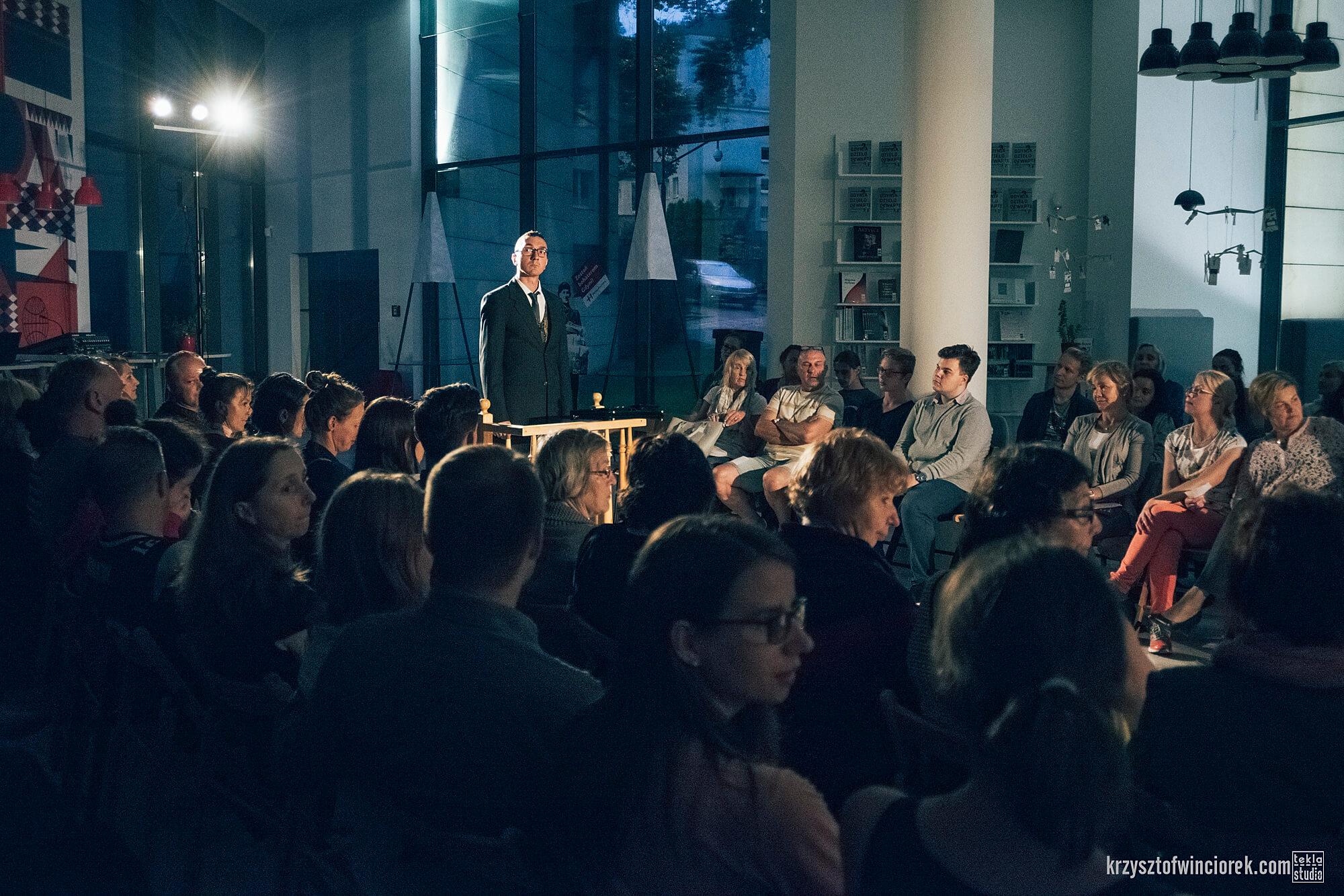Zdjęcie z festiwalu Pociąg do miasta. Aktor ubrany w ciemny garnitur stoi na środku przy drewnianej barierce. Po dwóch stronach zgromadzona publiczność.