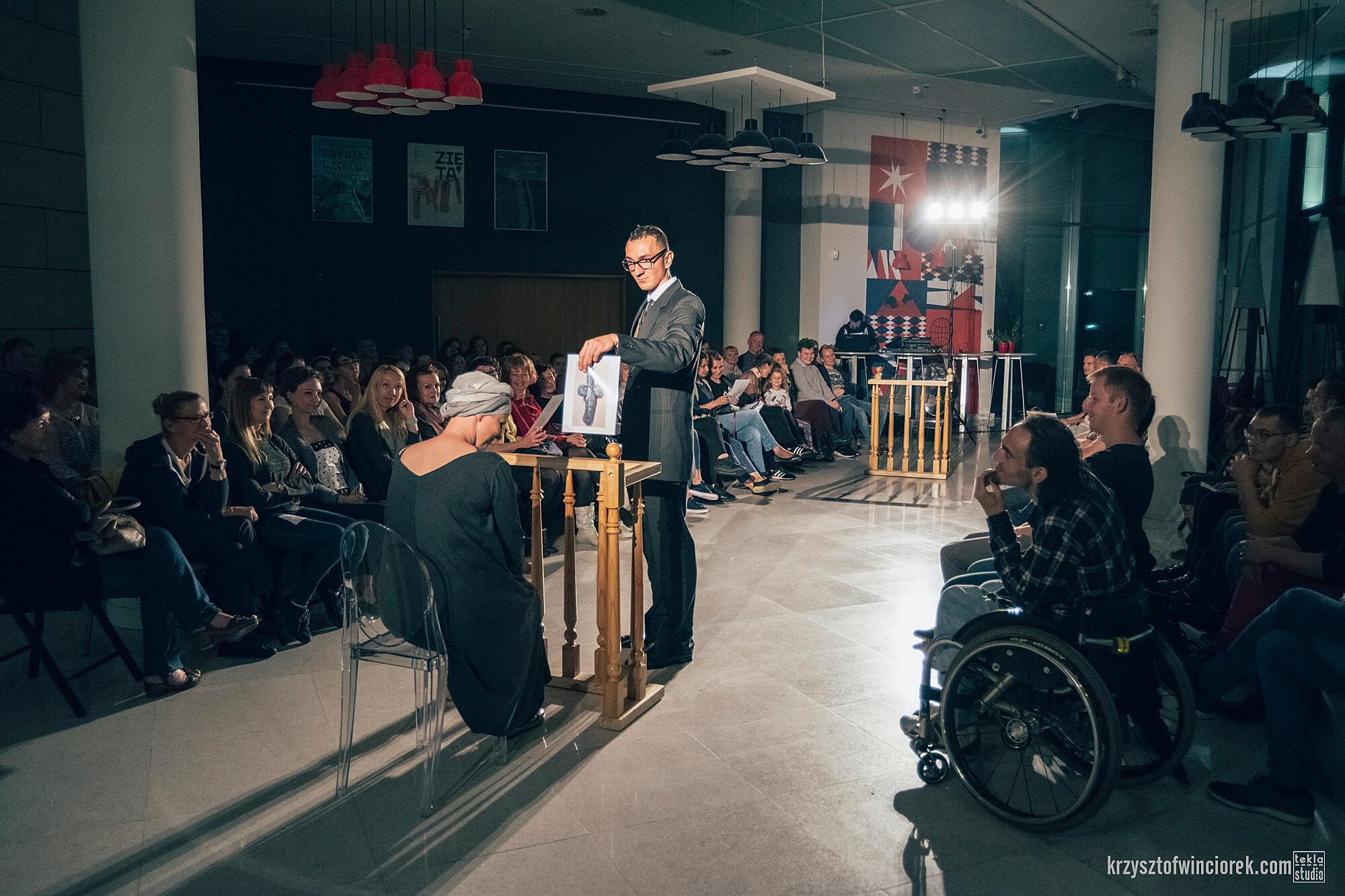 Zdjęcie z festiwalu Pociąg do miasta. Aktor ubrany w ciemny garnitur stoi na środku przy drewnianej barierce. Kobieta w turbanie siedzi przed nim na krześle. Mężczyzna pokazuje jej kartke papieru. Po dwóch stronach zgromadzona publiczność.