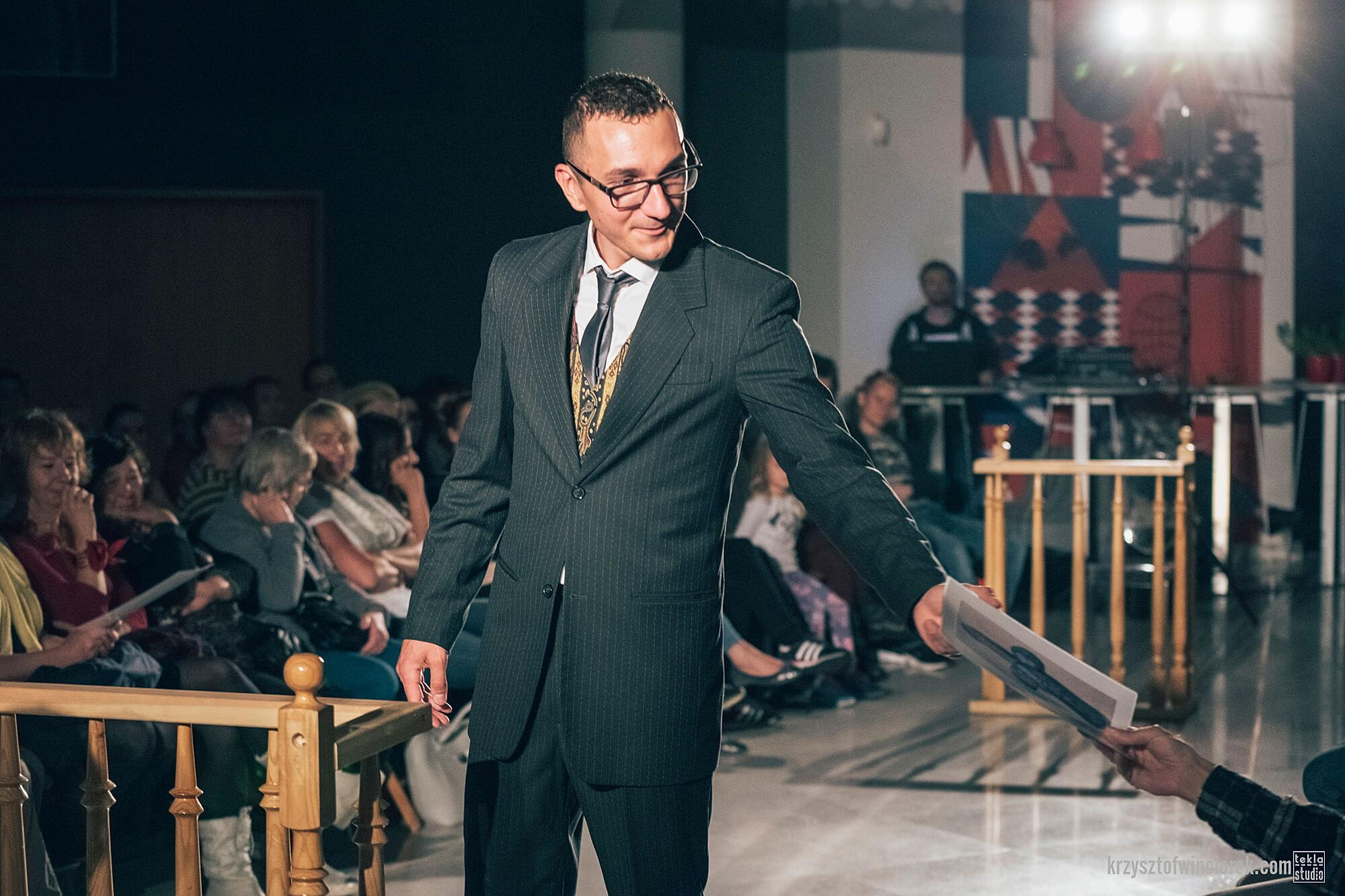 Zdjęcie z festiwalu Pociąg do miasta. Aktor w ciemnym garniturze i okularach, podaję kartkę papieru jednemu z widzów.