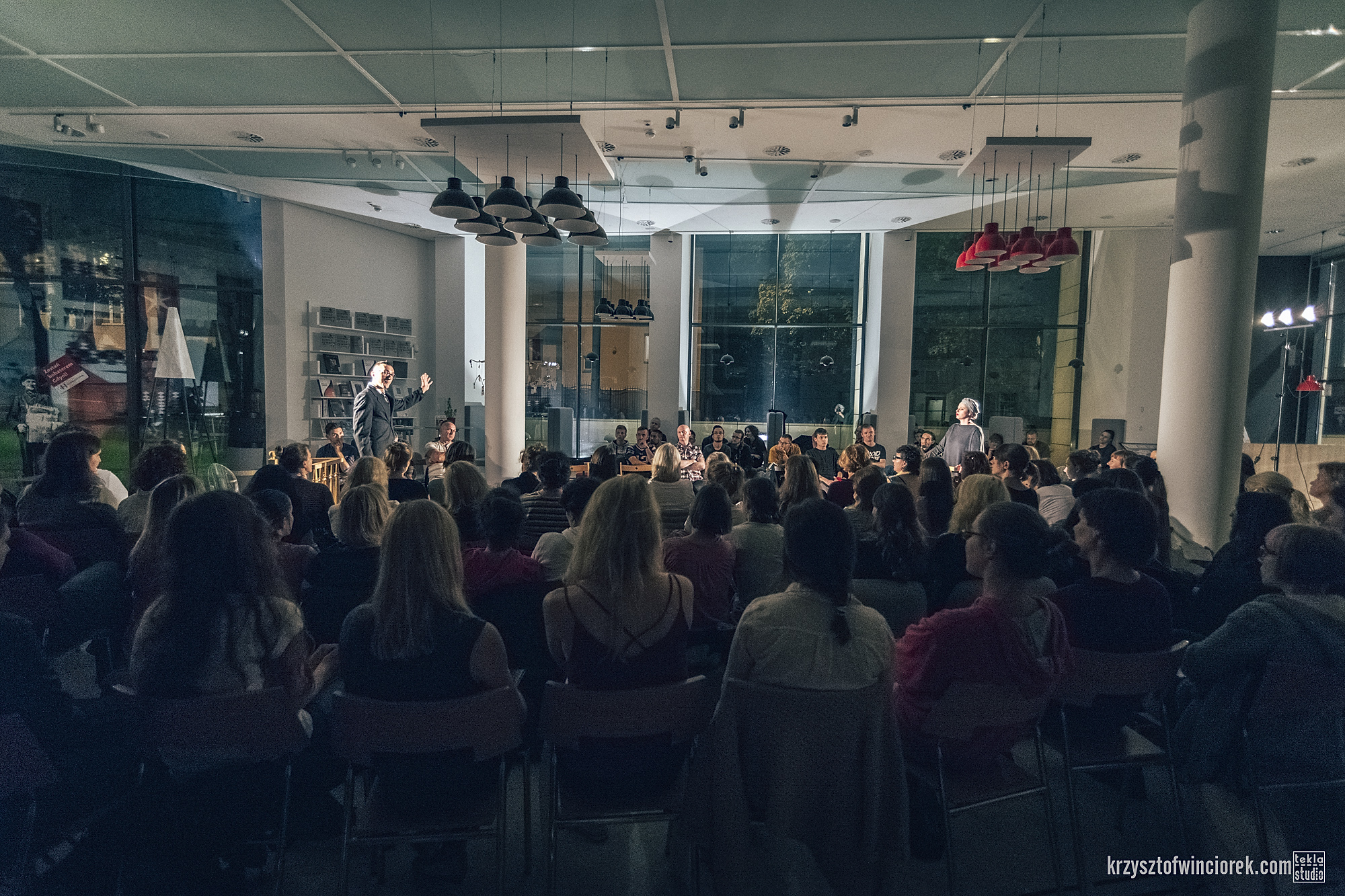 Publicznosc zgromadzona w dużym holu.