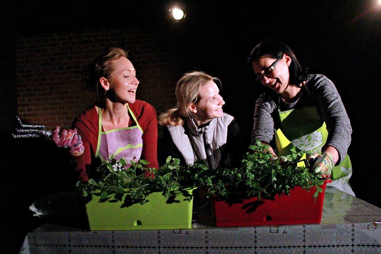 Zdjęcie z projektu Dzielnica cudów. Trzy aktorki pochylone nad doniczkami z roslinami. śmieją się do siebie.